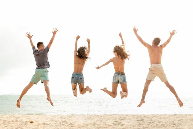 Gelukkige energieke groep vrienden die bij het strand tijdens de zomervakantie springen