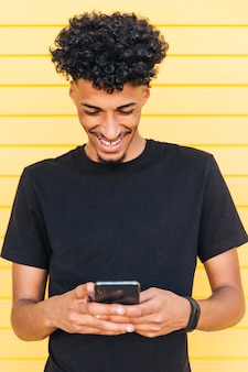 Gelukkige etnische mannelijke doorblazende telefoon