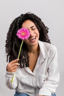 Gelukkige etnische vrouw met bloem tegen oog
