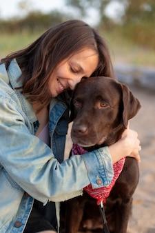 Gelukkige europese landvrouw met donker haar in een vintage spijkerjasje die een hond knuffelt en glimlacht