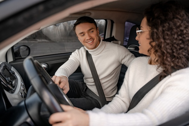 Gelukkige europese paar zitten in persoonlijke auto. jonge mooie krullende vrouw en volwassen man kijken naar elkaar en glimlachen. moderne vrouw als chauffeur. concept van auto rijden