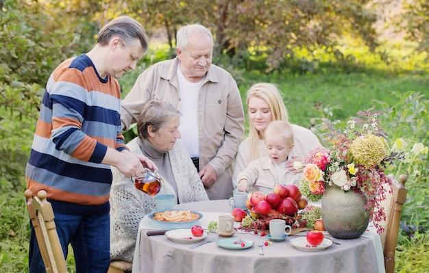 Gelukkige familie aan gedekte tafel met appeltaart in de tuin