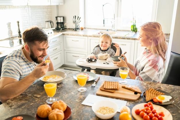 Gelukkige familie aan keukentafel in de ochtend