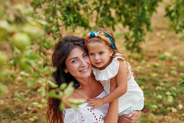 Gelukkige familie appels plukken op tuin. moeder en dochter in appelboomgaard