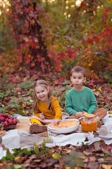 Gelukkige familie, babyjongen, meisje die taart eten bij een herfstpicknick met taart, pompoen, thee