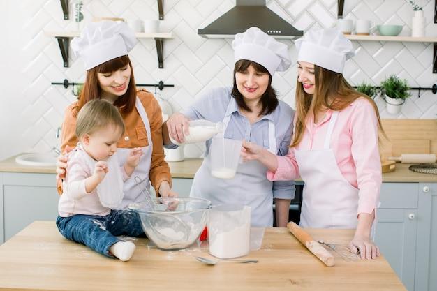 Gelukkige familie bakken in de keuken. oma met haar dochters en kleindochter die het deeg klaarmaakt, giet oma melk uit een fles in een maatglas