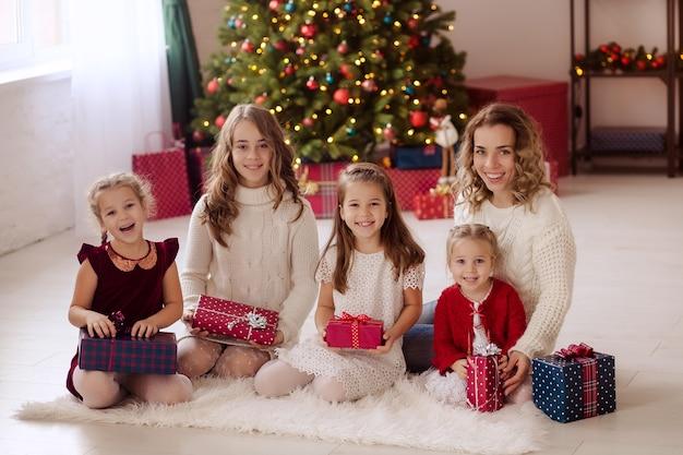 Gelukkige familie bij de kerstboom thuis met geschenken