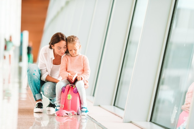 Gelukkige familie bij luchthavenzitting op koffer met instapkaart die op het inschepen wachten