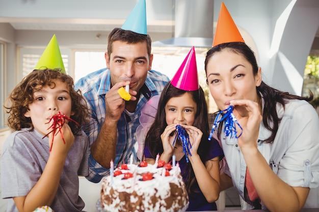 Gelukkige familie blazende partijhoorn tijdens verjaardagsviering