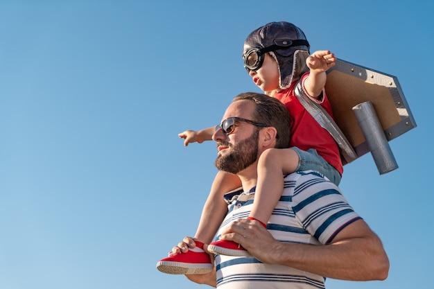 Gelukkige familie buiten plezier. vader en zoon spelen tegen blauwe zomer hemelachtergrond.