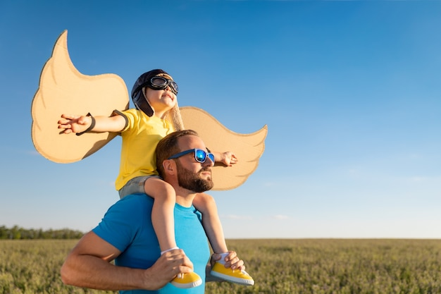 Gelukkige familie buiten plezier. vader en zoon spelen tegen blauwe zomerhemel. verbeelding en vrijheid concept