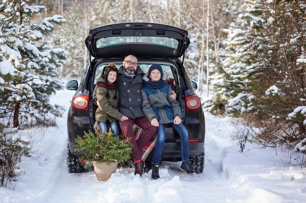 Gelukkige familie dichtbij zwarte auto bij snowly de winterdag. concept vakantie vakantie.