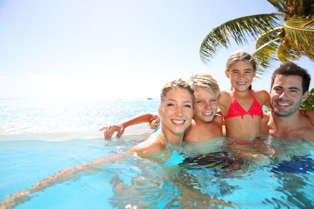 Gelukkige familie die bad van tijd in oneindigheidspool geniet