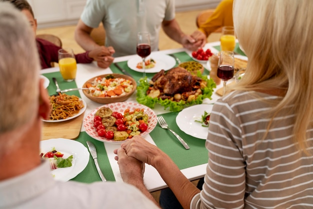 Gelukkige familie die bidt voordat ze samen gaan eten
