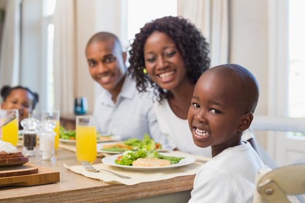 Gelukkige familie die bij camera bij lunch glimlacht