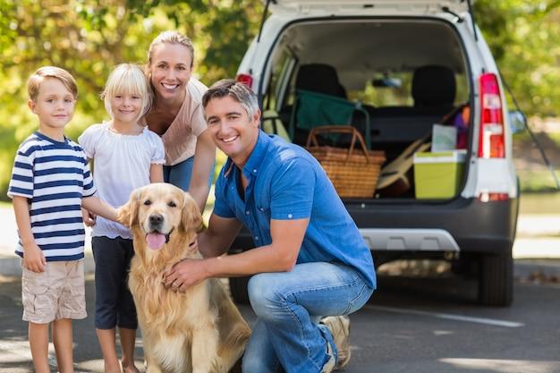 Gelukkige familie die bij de camera met hun hond glimlacht