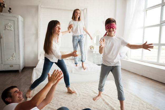 Gelukkige familie die bleekgele blinde thuis spelen