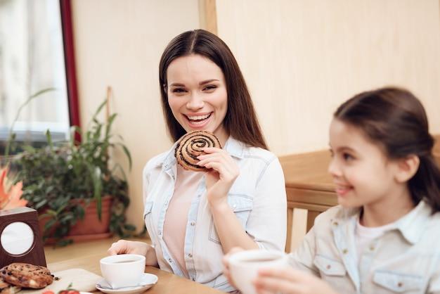 Gelukkige familie die cakes in cafetaria eet.