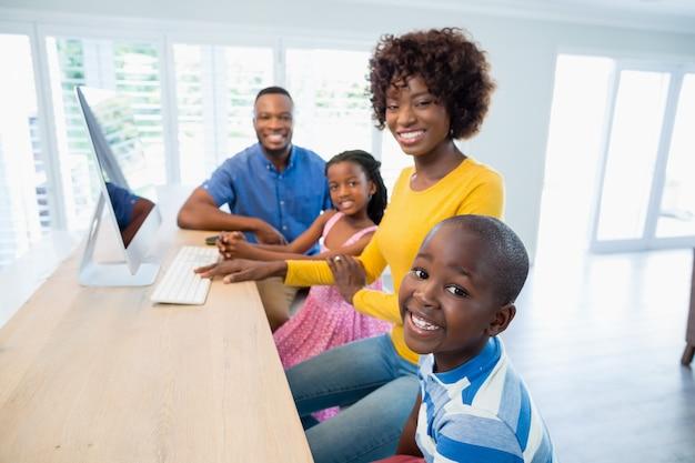 Gelukkige familie die computer in woonkamer thuis met behulp van