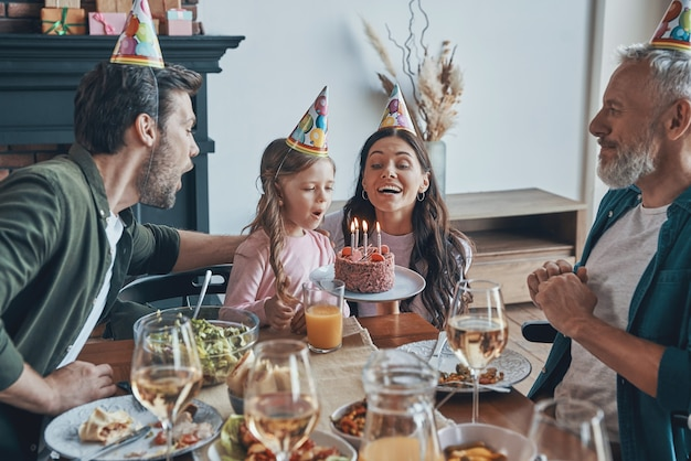 Gelukkige familie die de verjaardag van een klein meisje viert terwijl ze thuis aan de eettafel zit