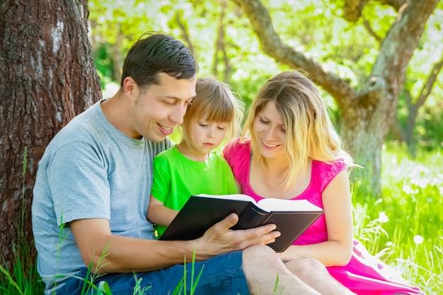 Gelukkige familie die een boek leest over de aard van de bijbel