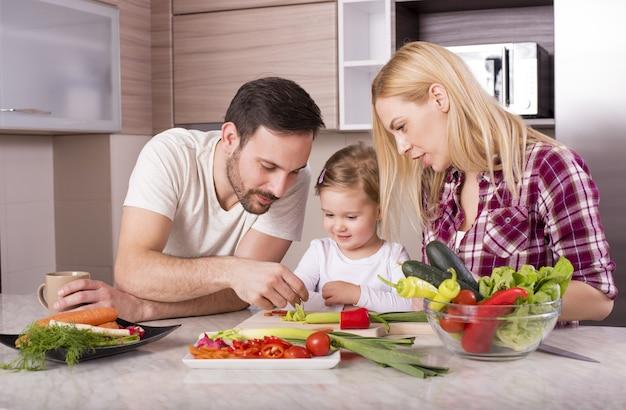 Gelukkige familie die een salade met verse groenten op het aanrecht maakt