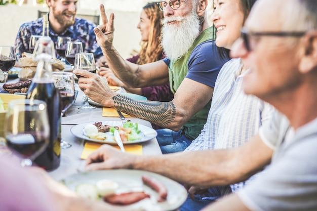 Gelukkige familie die en wijn eten eten bij barbecuediner in backyar openlucht