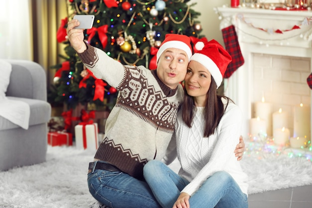 Gelukkige familie die foto maakt op de achtergrond van de kerstboom