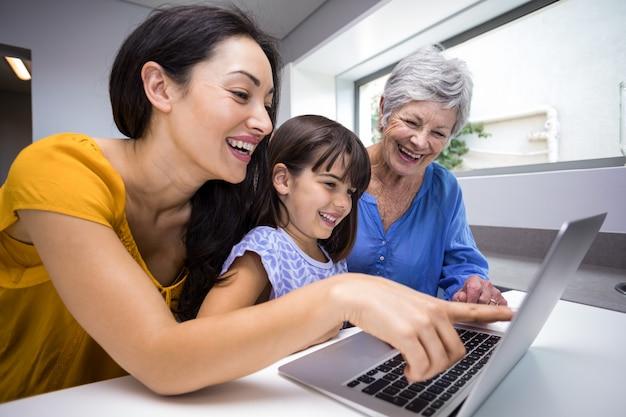Gelukkige familie die gebruikend laptop op elkaar inwerken
