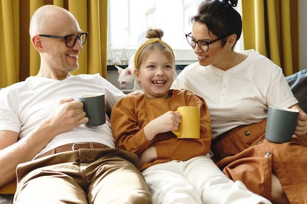 Gelukkige familie die hete thee drinkt in de woonkamer van hun gezellige appartement