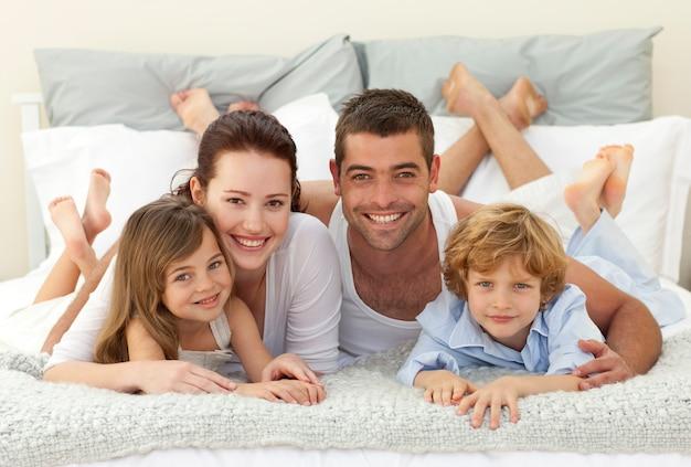 Gelukkige familie die in bed ligt en bij de camera glimlacht
