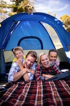 Gelukkige familie die in een tent ligt