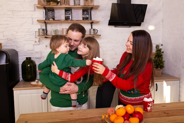 Gelukkige familie die in keuken thuis op kerstmis wacht