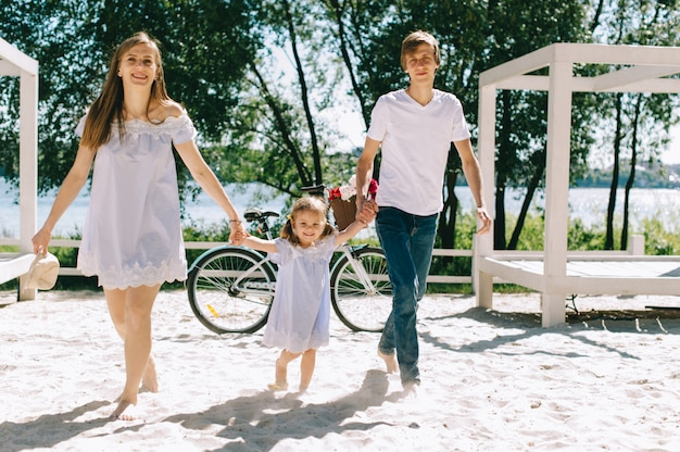 Gelukkige familie die in openlucht tijd samen doorbrengen. vader, moeder en dochter hebben lol en rennen