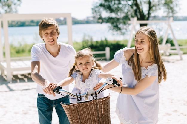 Gelukkige familie die in openlucht tijd samen doorbrengen. vader, moeder en dochter hebben plezier en spelen op