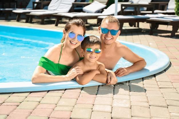 Gelukkige familie die in zwembad rust