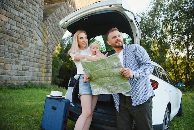 Gelukkige familie die kaart naast auto bekijkt