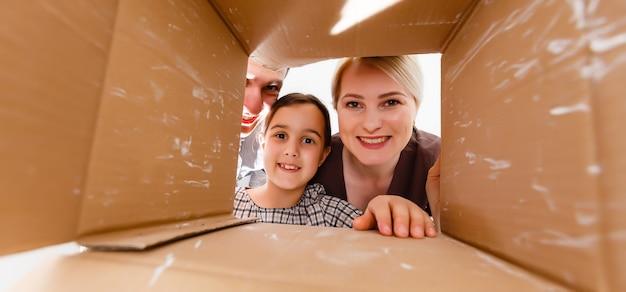 Gelukkige familie die kartonnen doos opent - bewegend concept