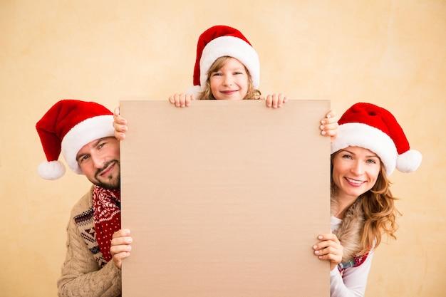 Gelukkige familie die kerstaffiche leeg houdt. kerst vakantie concept