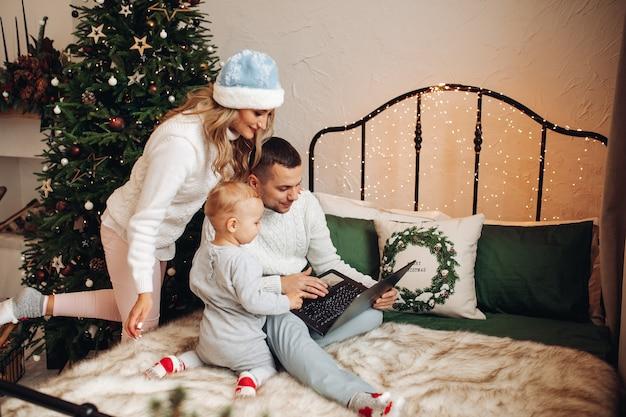 Gelukkige familie die kerstmis op bed viert en laptop gebruikt voor communicatie met familieleden.