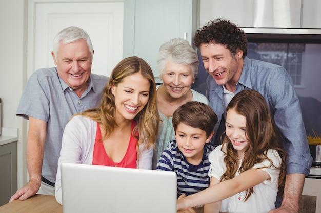 Gelukkige familie die laptop in keuken met behulp van