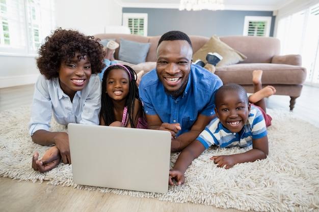 Gelukkige familie die laptop in woonkamer thuis met behulp van