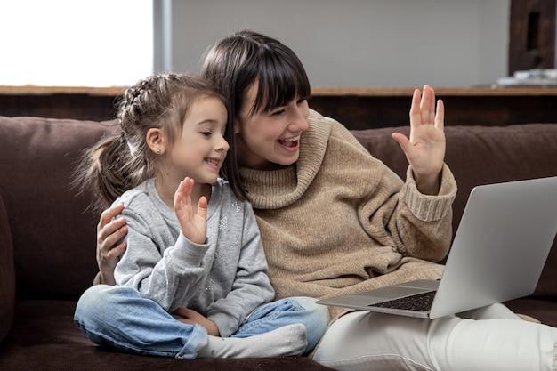 Gelukkige familie die laptopscherm bekijkt, maakt videogesprek op afstand. lachende moeder en meisje praten met webcamera op internet chat.