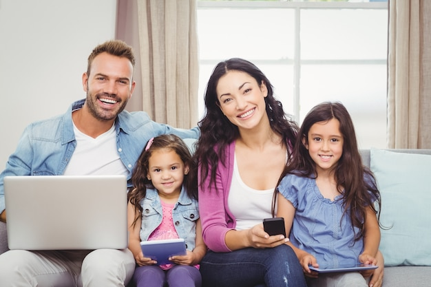 Gelukkige familie die moderne technologieën gebruiken terwijl het zitten op bank