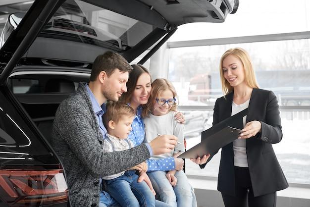 Gelukkige familie die nieuwe comfortabele zwarte auto in autosalon koopt