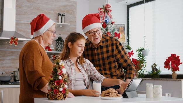 Gelukkige familie die online kerstvideo's uit de kindertijd bekijkt met behulp van tabletcomputer