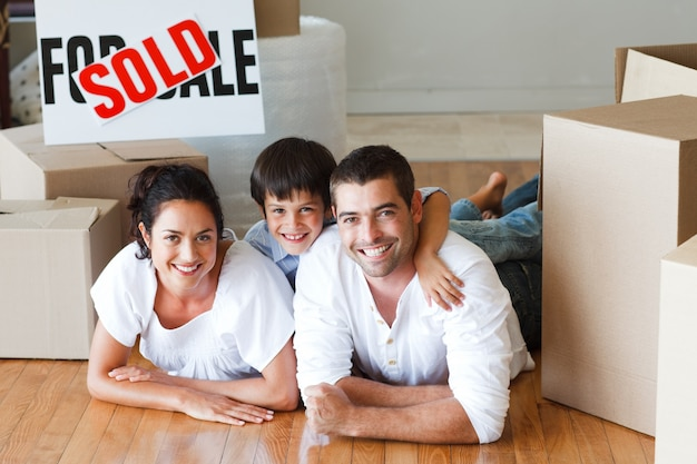 Gelukkige familie die op de vloer na het kopen van huis met dozen ligt