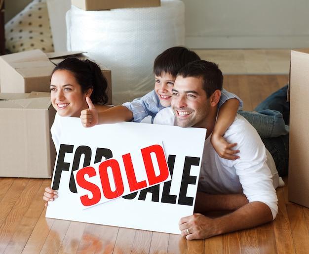 Gelukkige familie die op de vloer na het kopen van huis met omhoog duimen ligt
