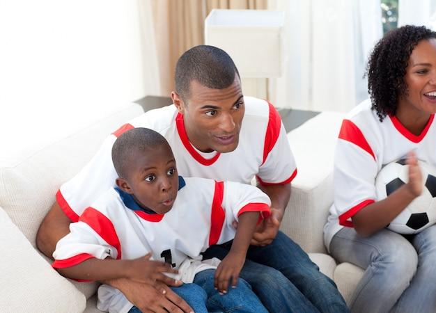 Gelukkige familie die op een voetbalwedstrijd letten