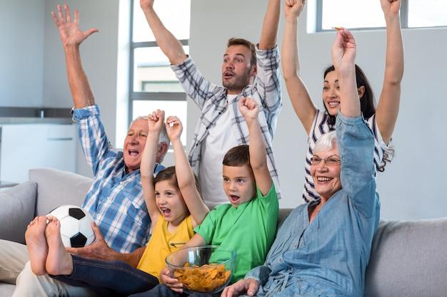 Gelukkige familie die op een voetbalwedstrijd thuis let